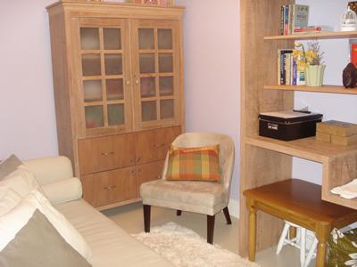 Sala de psicoterapia equipada com divã, espelho e ar condicionado, além do material para atendimento.